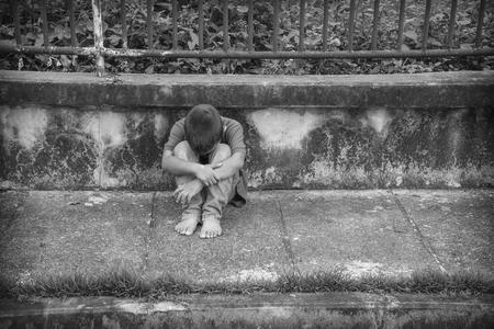 arme kinder: Eine junge Obdachlose asiatische Junge sitzt auf der Seite der Straße bedeckte sein Gesicht. Er ist mit einem hohen Risiko von Missbrauch und Menschenhandel