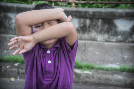 dissappointed: A young Asian boy covering his face with his hands, to avoid seeing physical abuse Stock Photo