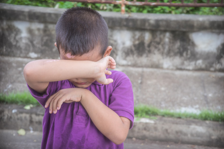 dissappointed: A young Asian boy covering his face with his hands so to not be the victim of physical abuse Stock Photo