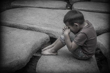 dissappointed: A young Asian boy sitting on rocks praying for a better life than the one he has which includes suffering and abuse