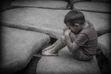 Młody chłopiec azjatyckich siedzi na skałach modląc się o lepsze życie, niż ta, którą posiada, który obejmuje cierpienia i przemocy