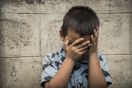 crying eyes: A young Asian boy covering his face with his hands, to avoid seeing physical abuse Stock Photo