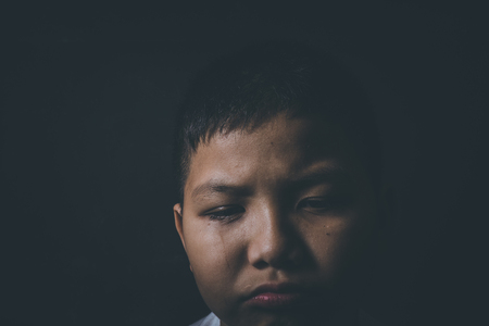 dissappointed: scared and alone, young Asian child who is at high risk of being bullied, trafficked and abused Stock Photo