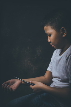 dissappointed: scared and alone, young Asian child who is at high risk of being bullied, trafficked and abused considering ending his life Stock Photo
