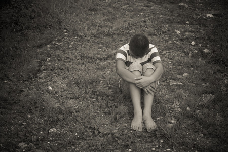 heaviness: scared and alone, young  Asian child who is at high risk of being bullied, trafficked and abused, selective focus Stock Photo