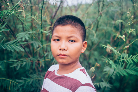 scared and alone, young  Asian child who is at high risk of being bullied, trafficked and abused, selective focus Stock Photo