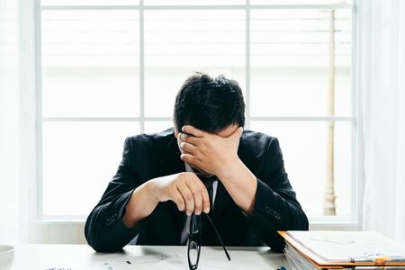 Een gespannen zakenman houdt zijn hoofd in wanhoop, omdat hij bang is dat hij faillissement moet indienen of in liquidatie gaat Stockfoto