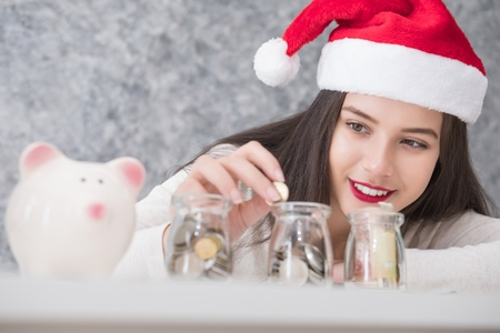 putting money in pocket: Beautiful young beautiful girl saving money for Christmas and holiday season. She is wearing a Santa hat, saving money concept Stock Photo