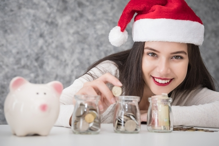 Beautiful young beautiful girl saving money for Christmas and holiday season. She is wearing a Santa hat, saving money concept Stock Photo