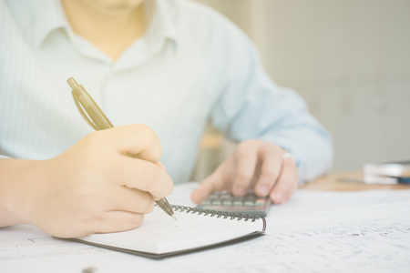 input device: Close up of a business man holding a pen and writing down his ideas for future investments Stock Photo