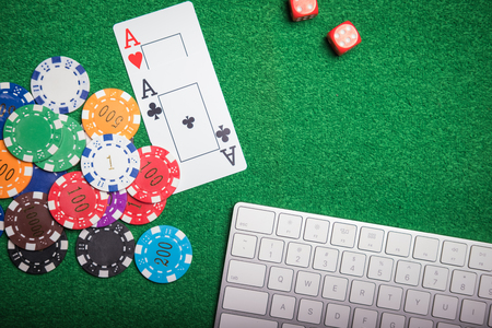 Gambling chips and cards on a green cloth Casino table Stock Photo