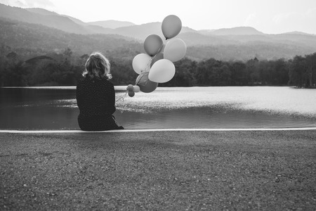 a women sitting alone on the road waiting for love, alone concept Stock Photo