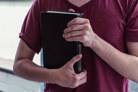 Closeup on a man holding a bible at shopping mall, believe concept