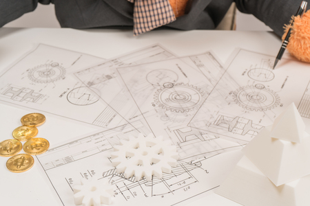 Architect or planner working on drawings for construction plans at a table Stock Photo