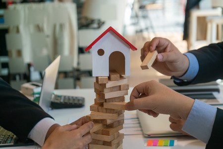 balancing the property sector in business, hands and a wooden house