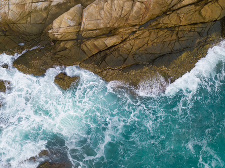 Sea waves breaking against  cliff viewed from above.