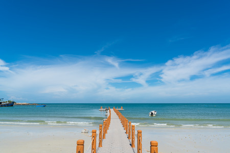 wooden pier leading out to the blue ocean