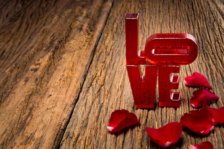 faded: Red resin letters forming word LOVE written and faded rose on rustic wood background