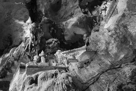 dao: Chiang dao cave wall with antique statue in black and white style