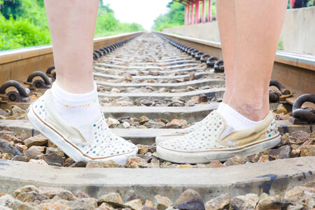 Closeup of male and female legs standing on rails train photo