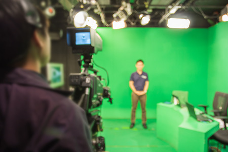 digital television: blur image A television presenter in a TV camera in studio a green