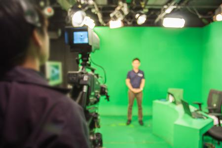 las imágenes borrosas Un presentador de televisión en una cámara de televisión en el estudio de un verde
