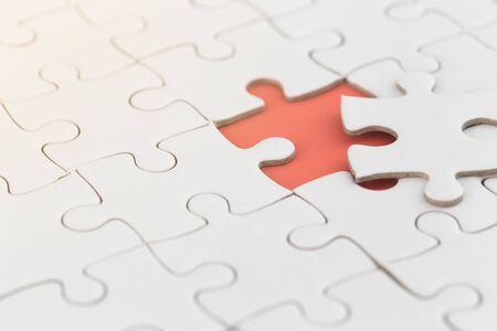 witte puzzel met ontbrekend stukje met oranje kleur.