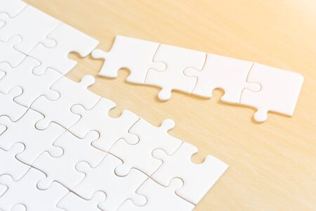 white connected jigsaw puzzle pieces on wooden table background. Standard-Bild - 138145914