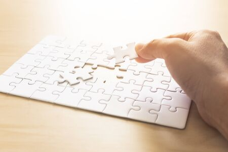 hands of man jigsaw puzzle connecting. Standard-Bild - 138145919