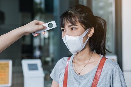 Officer checking fever with digital thermometer visitor asian woman before entering the building, coronavirus disease healthcare concept.