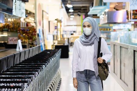 Asian muslim woman wearing medical mask for prevent dust and infection virus walking in the supermaket. Coronavirus(covid-19) concept.