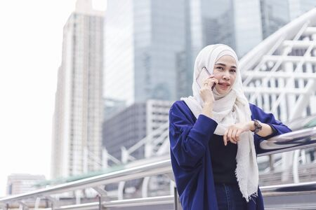 Beautiful asian muslim woman talking tetephone in city.