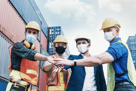 Teamwork engineer and technician foreman and partner wearing protection face mask, joining hands together in cargo container shipping area, work successful.