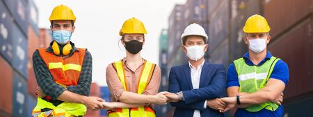 Teamwork engineer technician and foreman and partner wearing protection face mask and safety helmet in cargo container shipping area, shaking hands work successful.