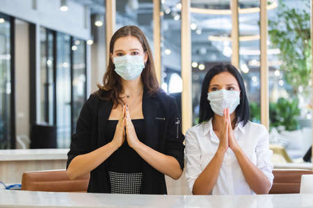 woman hotel receptionist wearing medical mask greeting thailand style.
