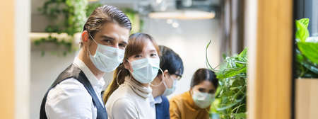 Group of business people with wearing hygienic mask prophylactic manager talking in meeting work room planning. Stock Photo