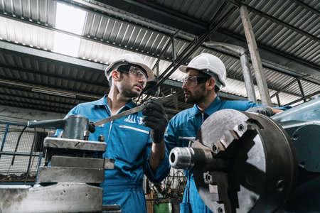 Engineer men wearing uniform safety in factory working machine lathe metal.