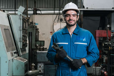 portrait of man engineering standing at factory with holding big wrench tool and looking at camera.