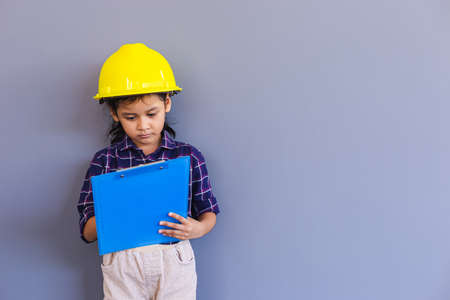 Asian little girl dress up engineering suit wearing helmet and holding a blue paperwork, engineering foreman and construction people concept.