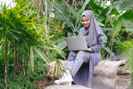 Asian muslim headscarf business women working with laptop in garden morning time.