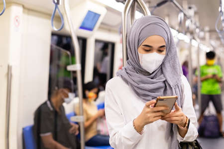 Asian muslim woman wearing medical face mask for prevent dust and infection virus, using smartphone in subway train transit system public.