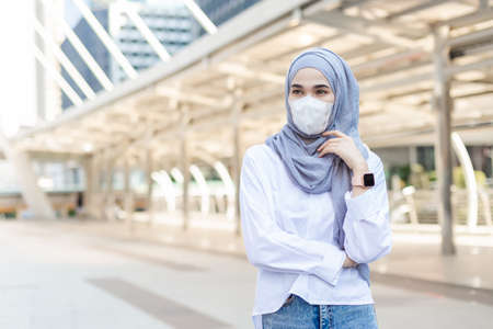 portrait young muslim woman wearing medical mask for prevent dust and infection virus standing street side in city.