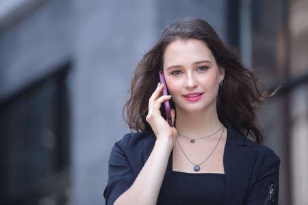 businesswoman calling on the mobile phone walk on city street. Stockfoto