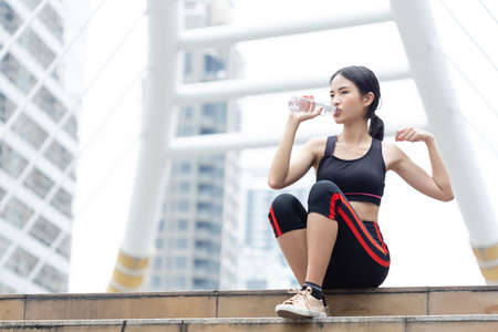 Asian beautiful woman athlete holding and drinking water in bottle after exercise , relax and exercise health concept.