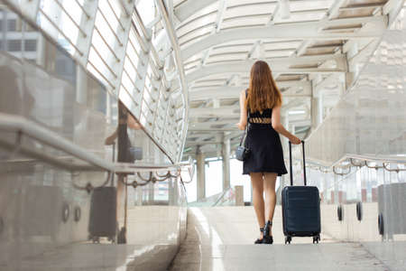 woman holding luggage for travel.