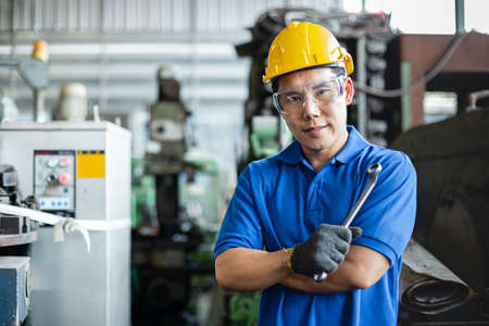 portrait image asian engineer men wearing uniform safety and holding wrench tool in factory. male professional maintenance repair machine at industrial.