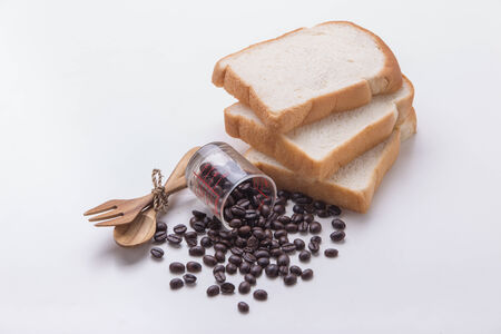 slice of bread with coffee Bean on white table photo