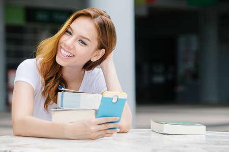 アジア女子学生が本を読みながら携帯電話を使用して。キャンパスで。