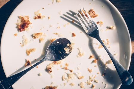 木製のテーブルの食糧スクラップを汚れた皿