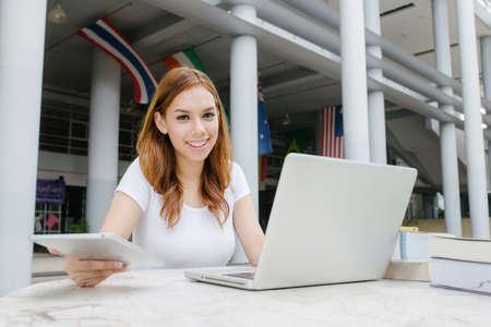 女性はキャンパス上のラップトップの使用します。